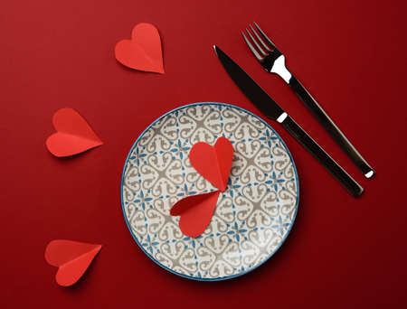 red paper heart lies in a white round ceramic plate, next to a fork and a knife, top view