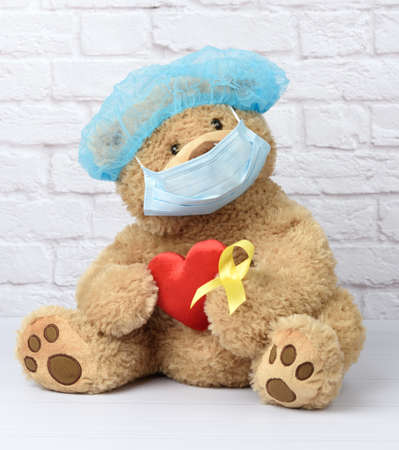 brown teddy bear holds in his paw a yellow ribbon folded in a loop, concept of the fight against childhood cancer.