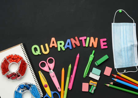 inscription quarantine from multicolored plastic letters and school supplies on black chalk board, concept of closing schools during a pandemic Foto de archivo
