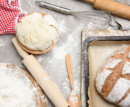 bread, kneaded dough of white wheat flour lies on a wooden plate and a wooden rolling pin, top view Imagens