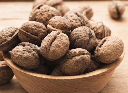 bunch of walnuts in a wooden plate on the table, close up