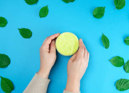 female hands of a young girl with smooth skin and round jar with cream, blue background with green leaves of raspberry, concept of spa treatments for the skin