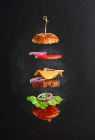 Flying ingredients of a classic cheeseburger sesame bun, onion rings, tomato slices and a juicy barbecue cutlet. layers of fast food on black chalk board background Imagens