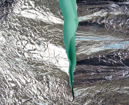 torn pieces of foil on a green background, close up