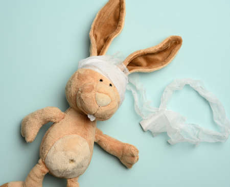 plush beige rabbit with a bandaged head with a white medical bandage on a blue background, top view