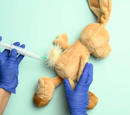 plush rabbit and two female hands of a doctor injecting an injection on a blue background, the concept of vaccination and treatment