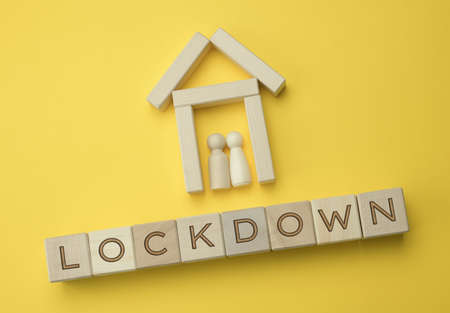 two wooden figures of a family inside a decorative house and an inscription on wooden blocks lockdown, yellow background. Self-isolation concept to prevent the spread of the virus