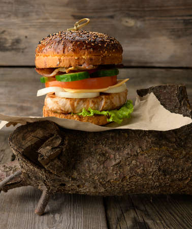 cheeseberger with bun, meat and vegetables on a wooden background, fast food