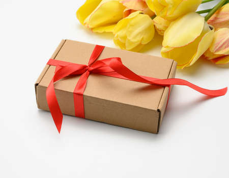 yellow tulips and square box tied with red ribbon on white background, festive background for mother's day, birthday