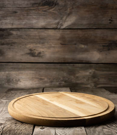 empty round wooden cutting kitchen board on wooden background, pizza board 免版税图像