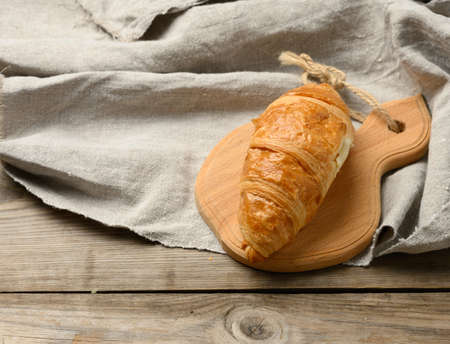 baked croissant on wooden board, wooden gray table, close up, top view