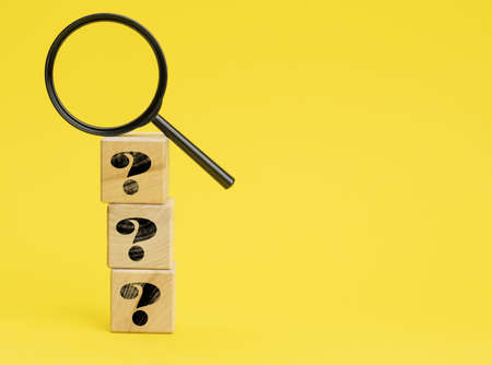 wooden cubes with question marks and a magnifying glass on a yellow background. The concept of finding answers to unknown questions, solving a problem. Find information 免版税图像