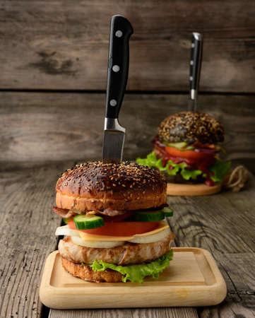 cheeseburger with bun, meat and vegetables on a wooden background, fast food and knife