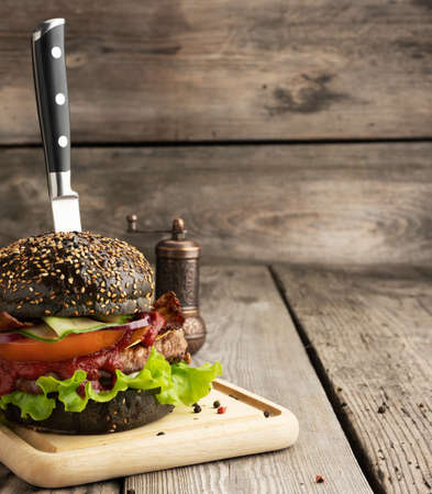 cheeseburger with black bun, meat and vegetables on a wooden background, fast food 免版税图像