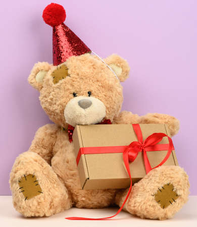 cute brown teddy bear in a red cap sits and holds a brown box with a gift, festive background