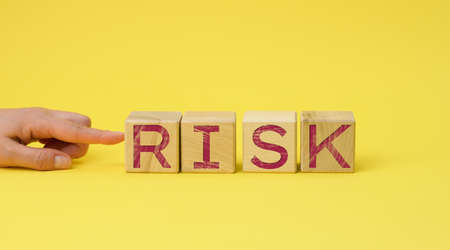 wooden cubes with the inscription risk on a yellow background. Risk reduction concept, reinsurance. How to avoid losses, unknown new beginnings in business and life