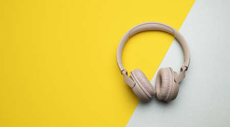 pink wireless headphones on a gray-yellow background, top view. Modern gadget for listening to music