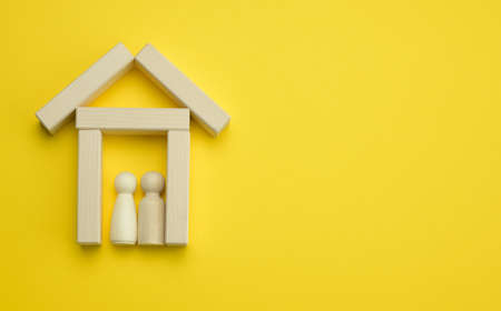 wooden miniature house on a yellow background. The concept of buying and selling a house, renting and leasing real estate, insurance, a place for an inscription