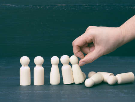the hand pushes the wooden figures of men, they fall in different directions. The concept of psychological pressure on a person, burnout. Dominance, repression and elimination of competitors