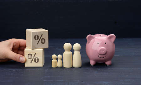 wooden family figurines and pink ceramic piggy bank on blue background. Concept of accumulating cash for buying a house and a car, money in the bank at interest, safe storage 免版税图像
