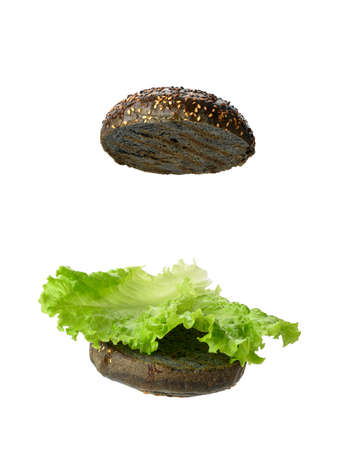 green lettuce leaf lies on a half of a black round bun, food is isolated on a white background