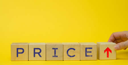 inscription price on wooden cubes and up arrow on yellow background. The concept of price increases, inflation, the possibility of additional earnings on a margin