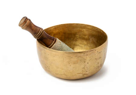 copper singing bowl and wooden clapper on a white background. Musical instrument for meditation, relaxation, various medical practices related to biorhythms, in yoga