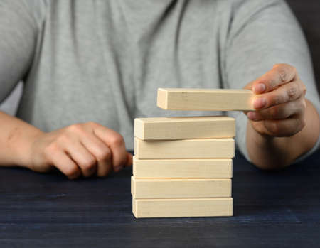 female hand puts wooden blocks on top of each other. Goal planning concept, new knowledge, strategy and management Archivio Fotografico