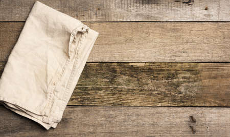 folded beige linen towel on a table made of old gray wooden boards, top view, copy space