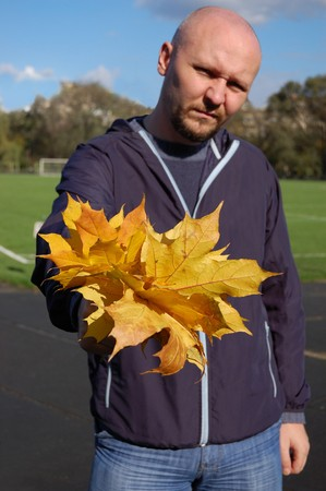 Serious young man holds autumnal bouquet Stock Photo - 4344904