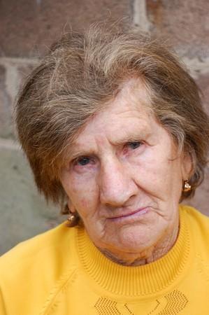 sad old woman: Triste mujer de edad en la blusa de color amarillo
