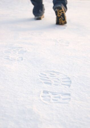 Fresh tracks from man boots on clean snow photo