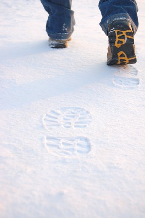 Fresh footprints from man boots on snow photo