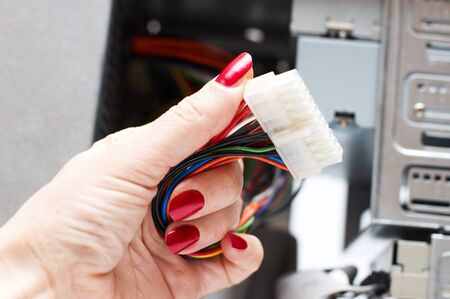 Woman hand assembles computer cable into system unit Stock Photo - 4407258