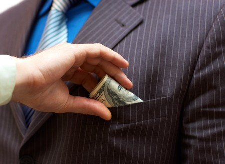 putting money in pocket: Man putting money into businessman side pocket