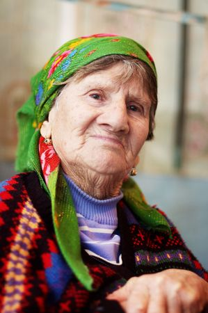 Smiling old woman in coloured sweater and orange bright headscarf Stock Photo - 4672287