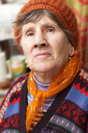 Portrait of old woman in red beret and coloured sweater photo