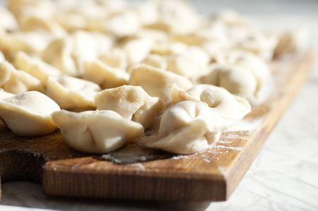 Uncooked meat dumplings on kitchen preparation table photo