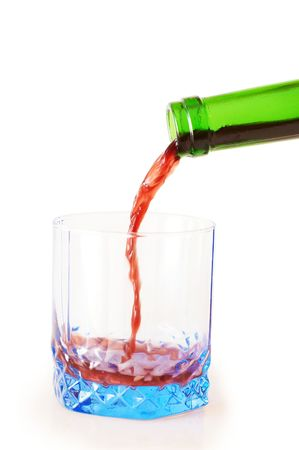 Red wine pouring down from a wine bottle into blue glass Stock Photo - 4920854