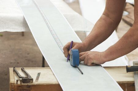Construction activity: worker drawing line on plastic panel photo