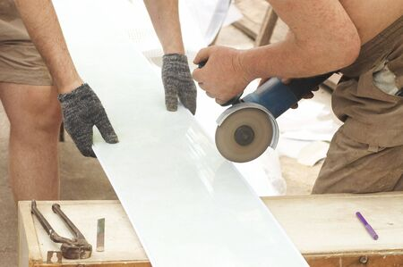 circ saw: Construction activity: two workers sawing  plastic panel  Stock Photo