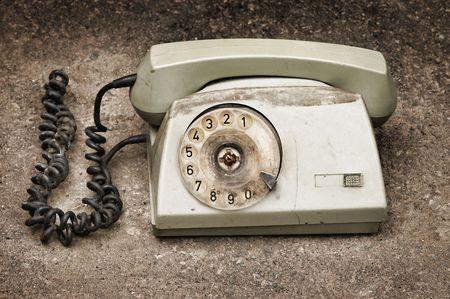 desaturated: Grunge: old broken phone on asphalt background