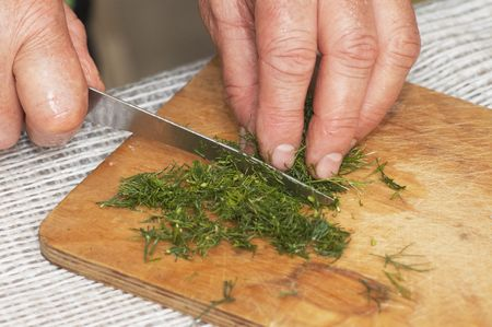 Cooking: woman hands cutting dill by kitchen knife  photo