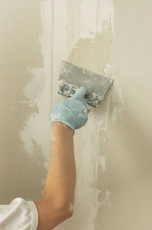 glazing: Woman hand with palette knife glazing wall  Stock Photo