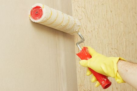 lubricate: Hand in glothes lubricating wall on glue for wallpaper