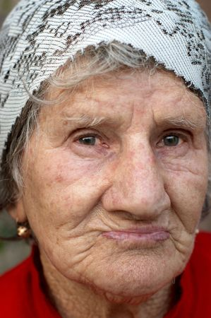 Portrait of Sad old woman in the headscarf photo