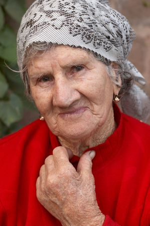 Smiling old woman in red sweater and headscarf photo