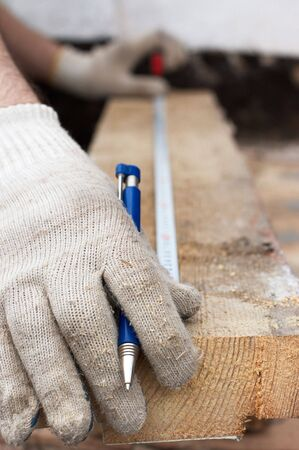 metre: Hands in protective gloves with pen and Metre measure ruler