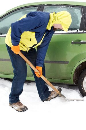 Man digging car wheels from the snow photo