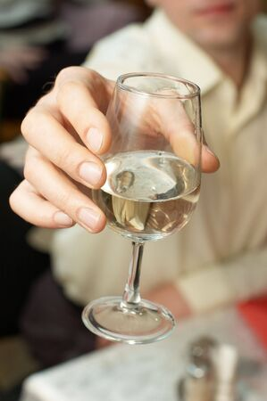Caucasian man propose a toast with a glass of white wine photo